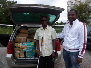 """Bodja MBOUDO, président de """"Village interactif"""" (à droite) et son ami kinésithérapeute lors du chargement des livres."""